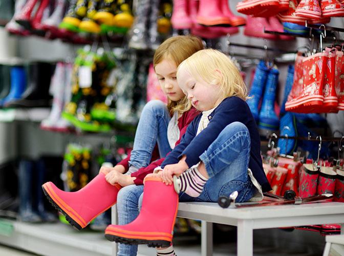 Barn som prøver gummistøvler i butikk. Foto.