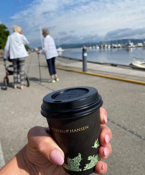 Hånd med kaffekopp. Damer på tur langs brygga. Foto.